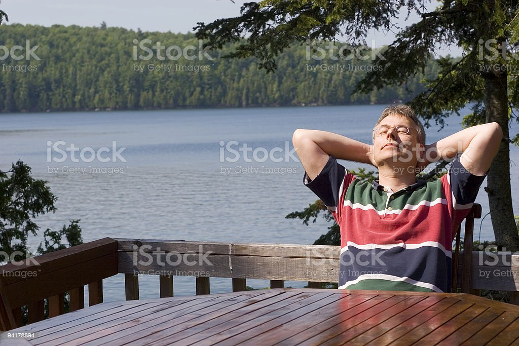 Man relaxing by a lake stock photo
