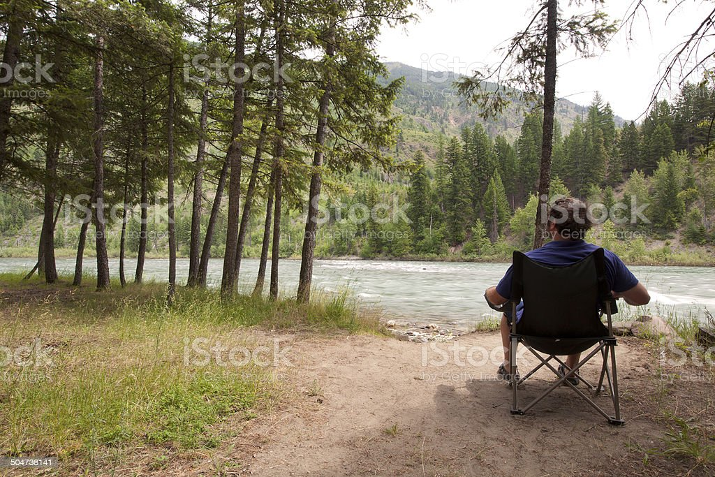 Man relaxing by a river stock photo