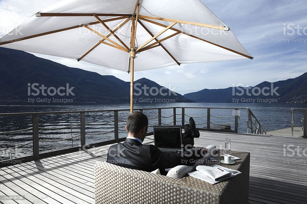 Man relaxing by water under umbrella with laptop  royalty-free stock photo