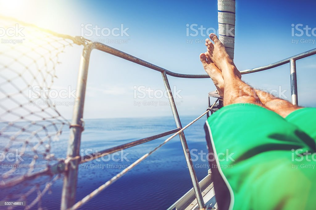 Man relaxing during cruise on a Sailing Boat stock photo