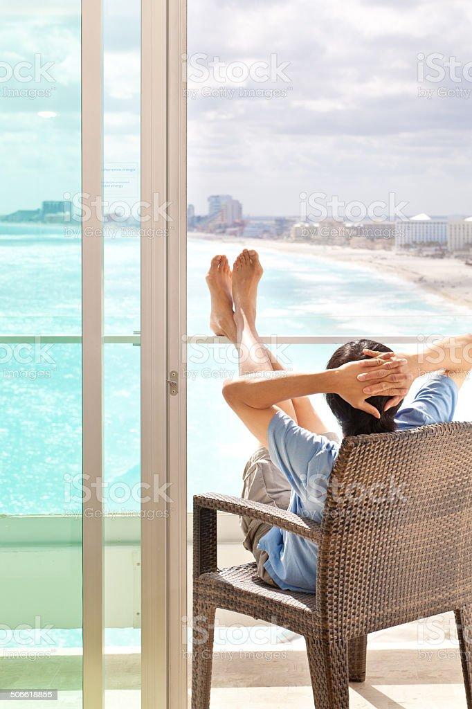 Man Relaxing, Enjoying Hotel Balcony Sea View on Beach Vacation stock photo