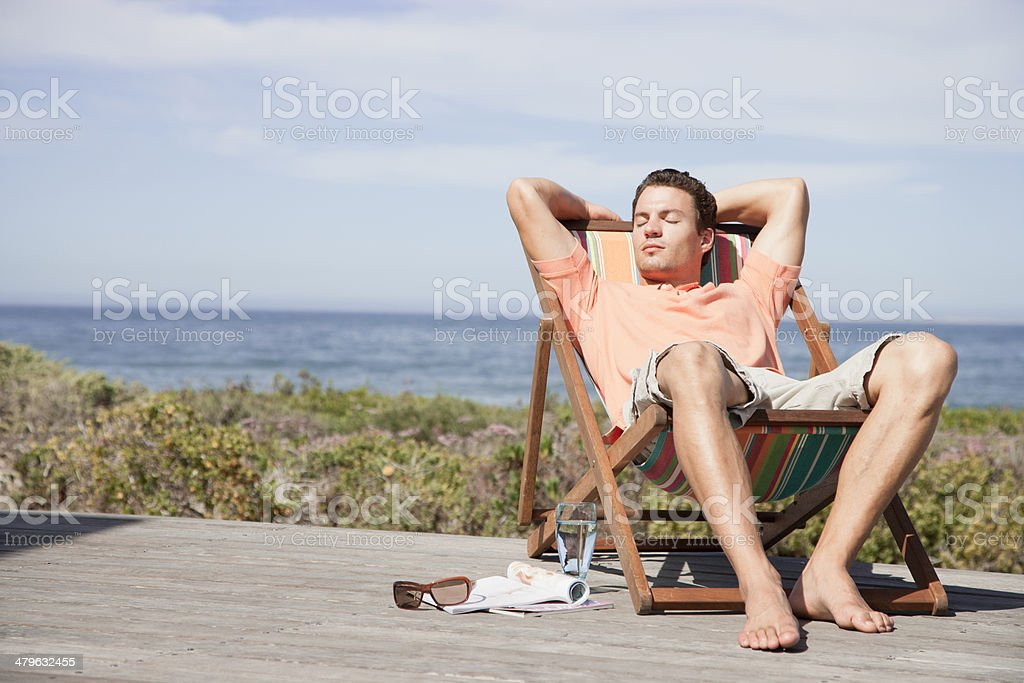 Man relaxing in a lounge chair stock photo