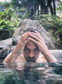 Man relaxing in a rainforest hot spring, New Zealand