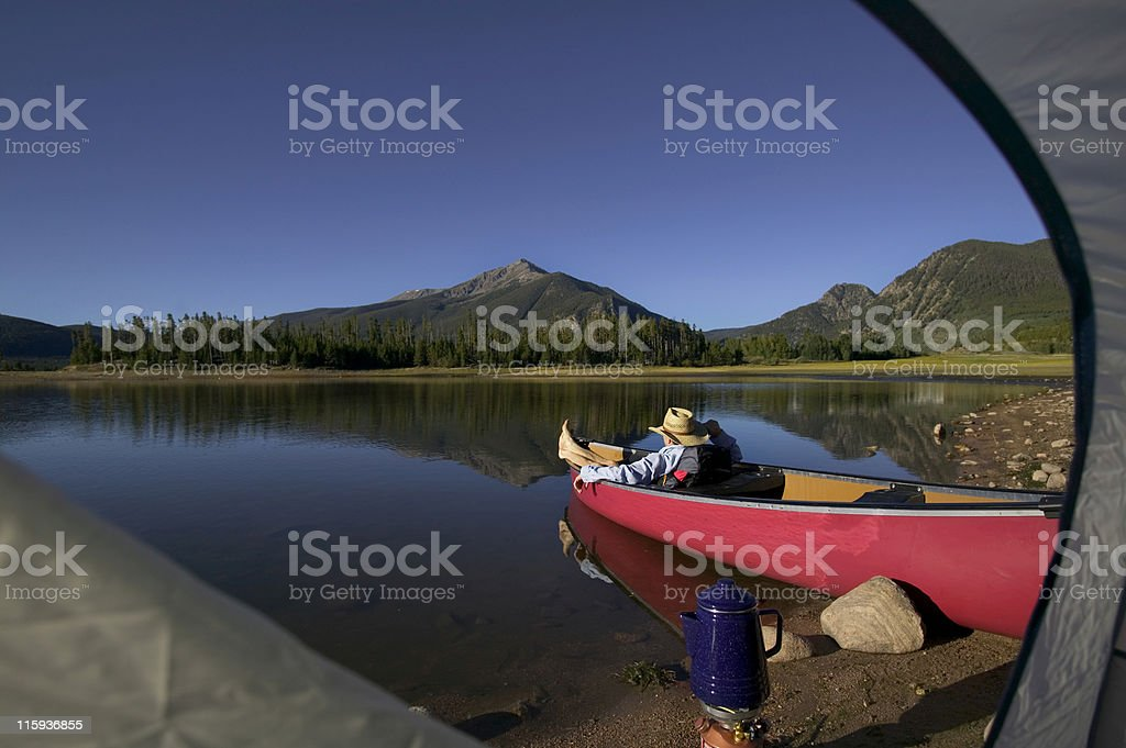 Man Relaxing in Canoe on Mountain Lake Framed by Tent royalty-free stock photo