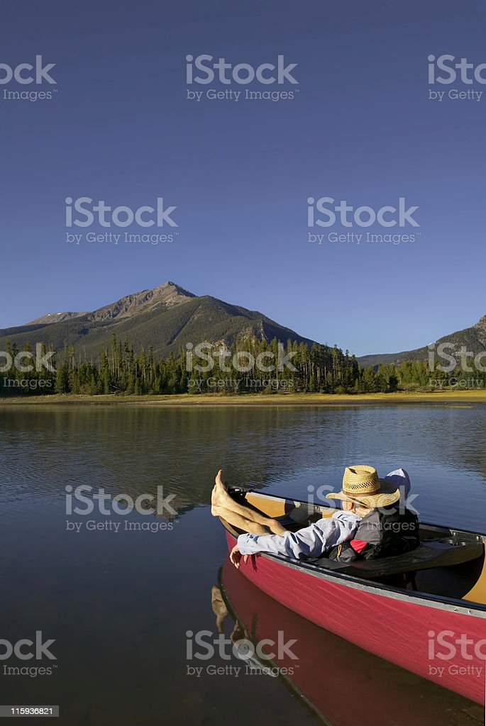 Man Relaxing in Canoe with Mountain View royalty-free stock photo