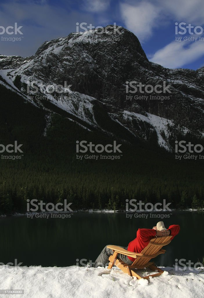 man relaxing in lounge chair at snowy lake with mountain royalty-free stock photo
