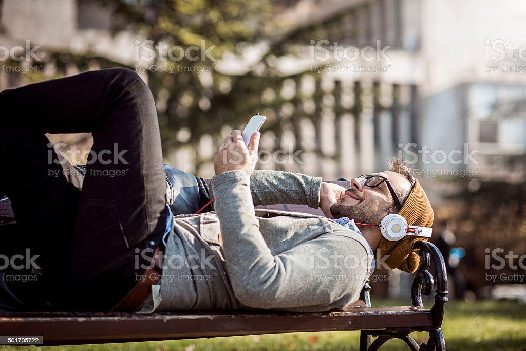 man relaxing in the park listening to the music stock photo