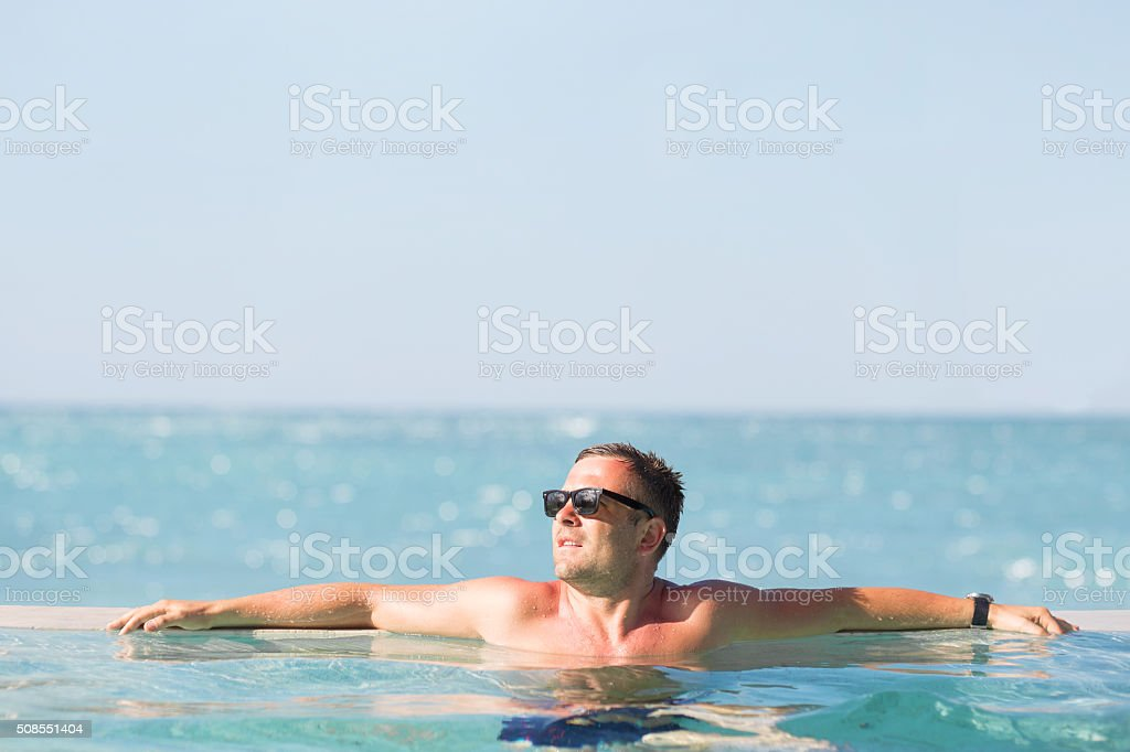 Man relaxing in the pool stock photo