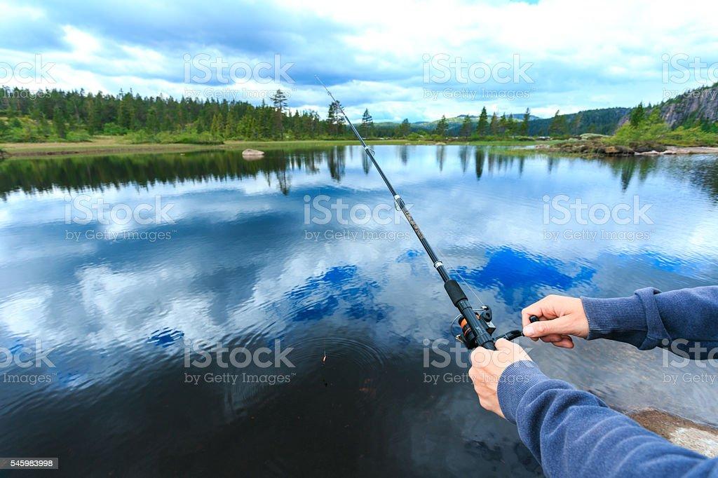 Man relaxing near mountain lake at summer stock photo