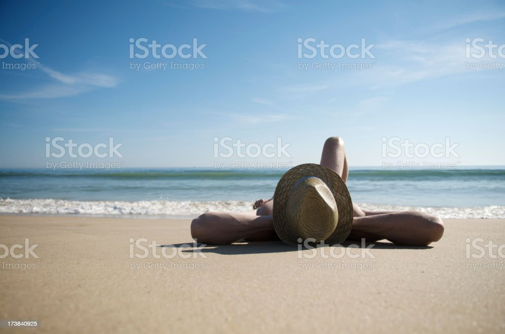 Man Relaxing on Deserted Beach Wearing Hat royalty-free stock photo