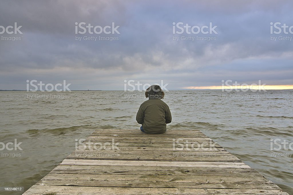 Man relaxing on jetty with dramatic sky royalty-free stock photo