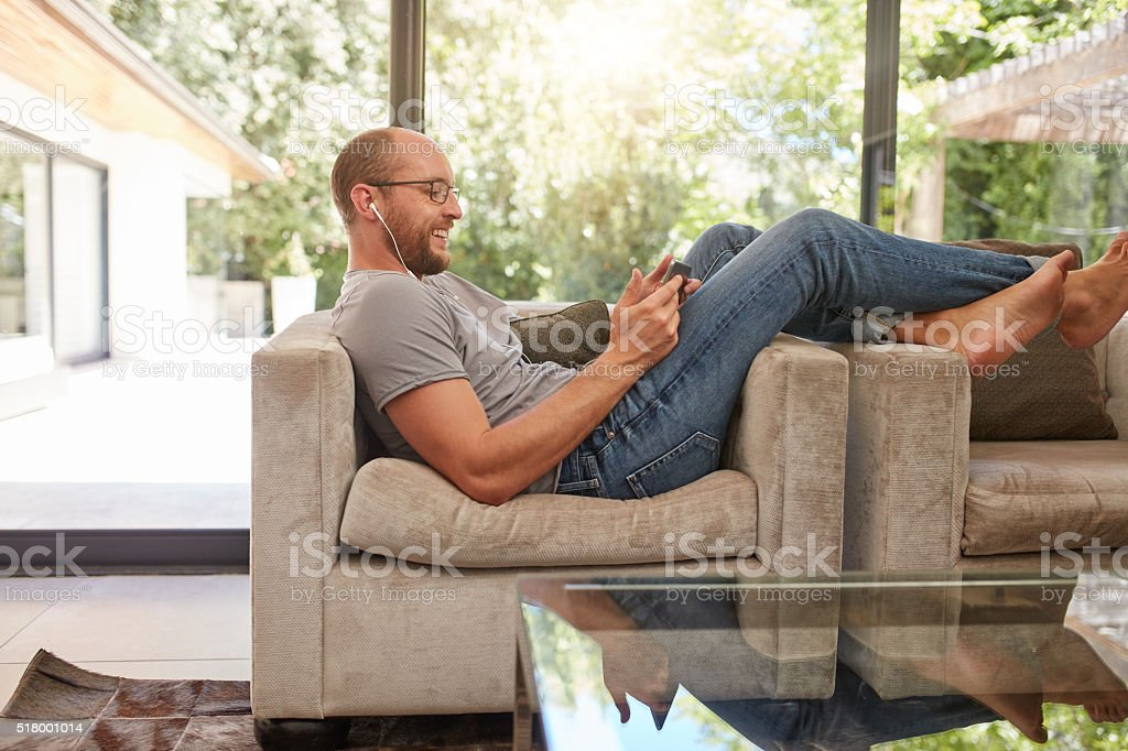 Man relaxing on sofa using tablet PC stock photo