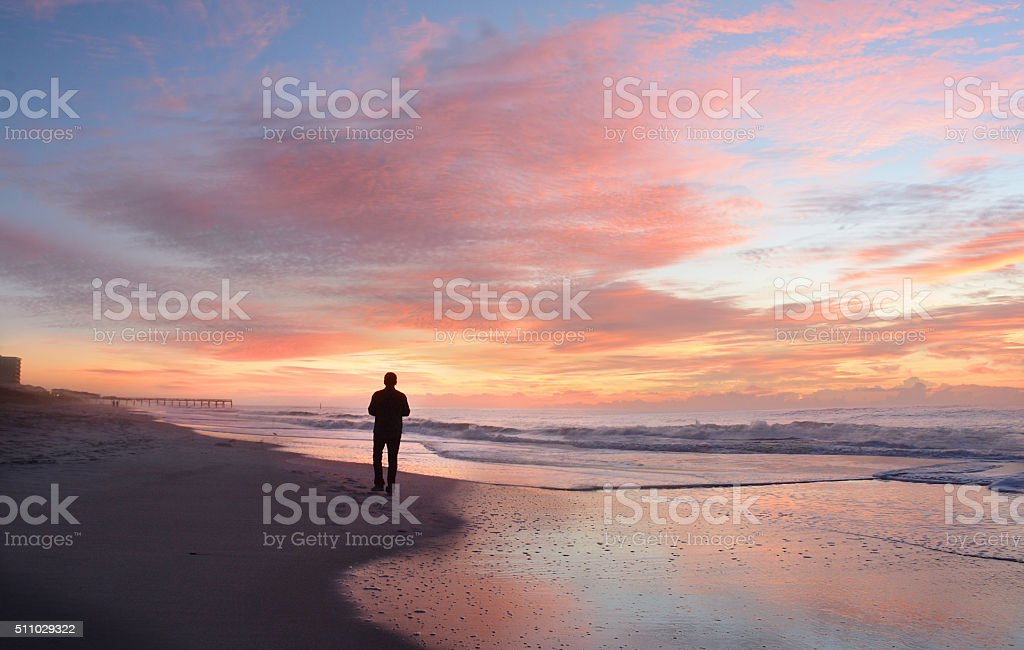 Man relaxing on the beach at sunrise. stock photo