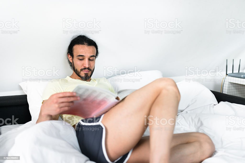 man relaxing on the bedroom stock photo