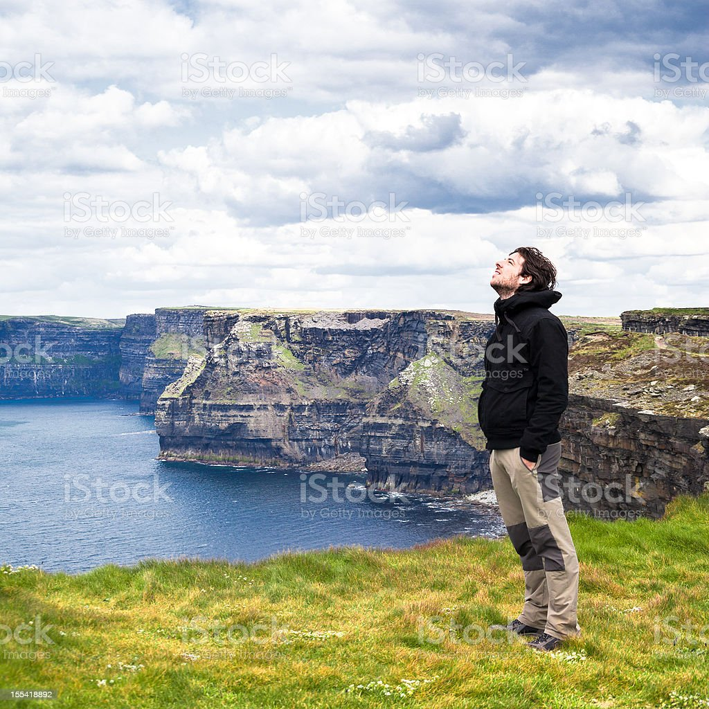 Man Relaxing on the Cliffs of Moher stock photo