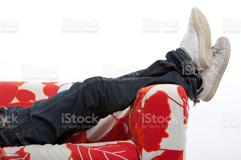 A man relaxing on the sofa wearing white sneakers and jeans royalty-free stock photo