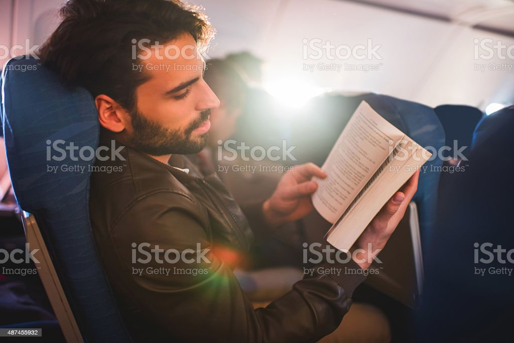 Man relaxing while reading a book in airplane. stock photo