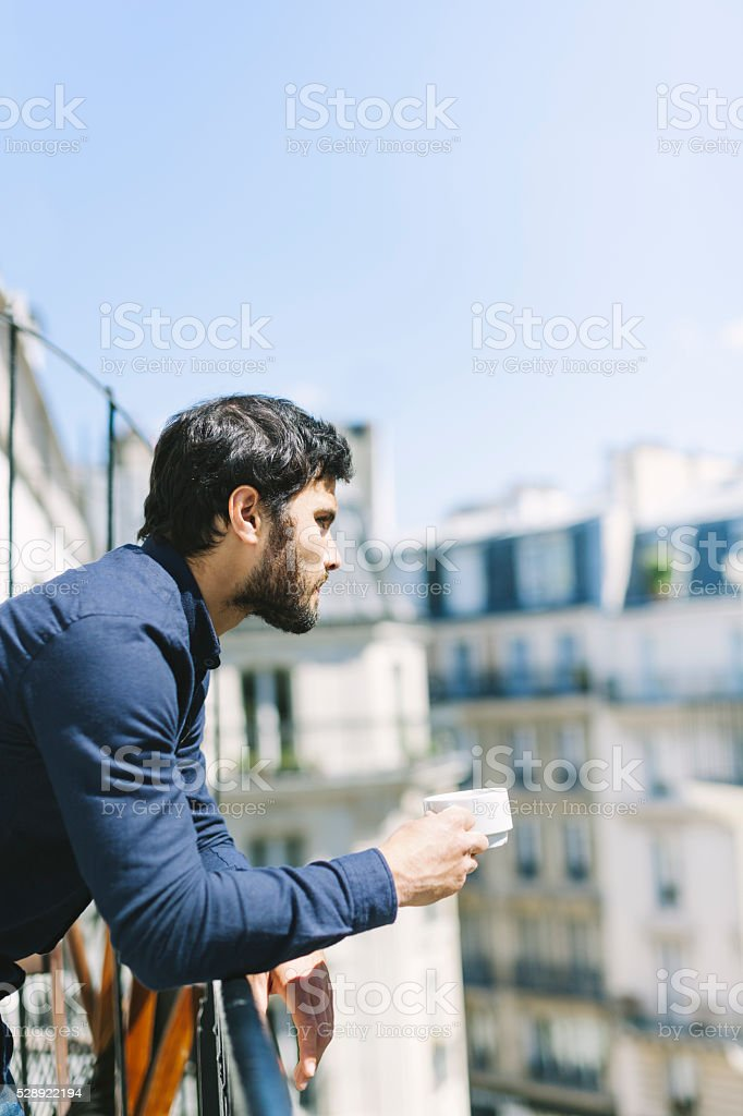 Man Relaxing with a Cup of Coffee on a Balcony stock photo