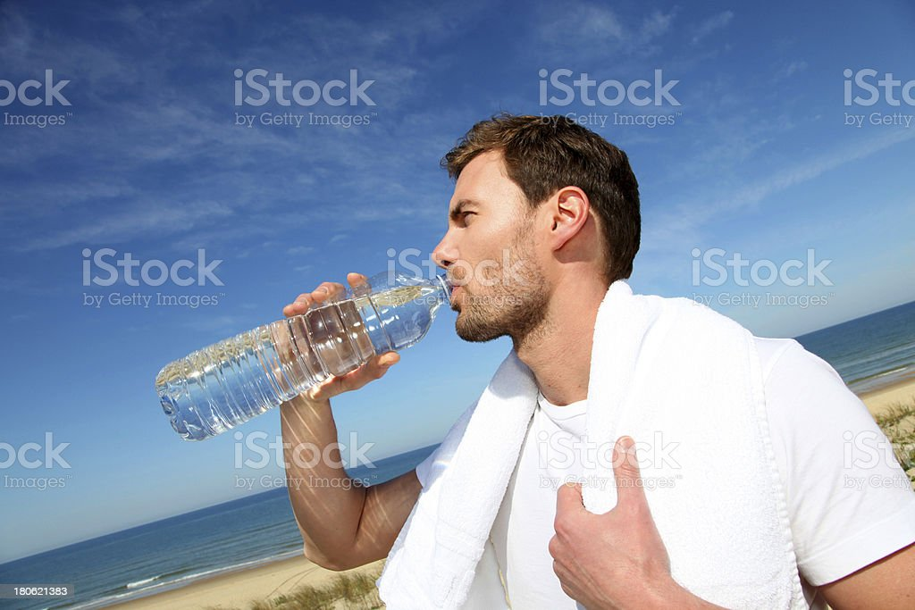 Man relaxing with a drink after running royalty-free stock photo