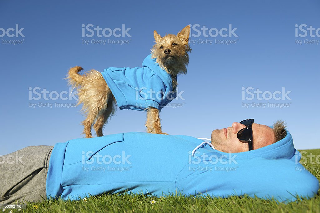 Man Relaxing with Best Friend Dog in Matching Hoodies stock photo