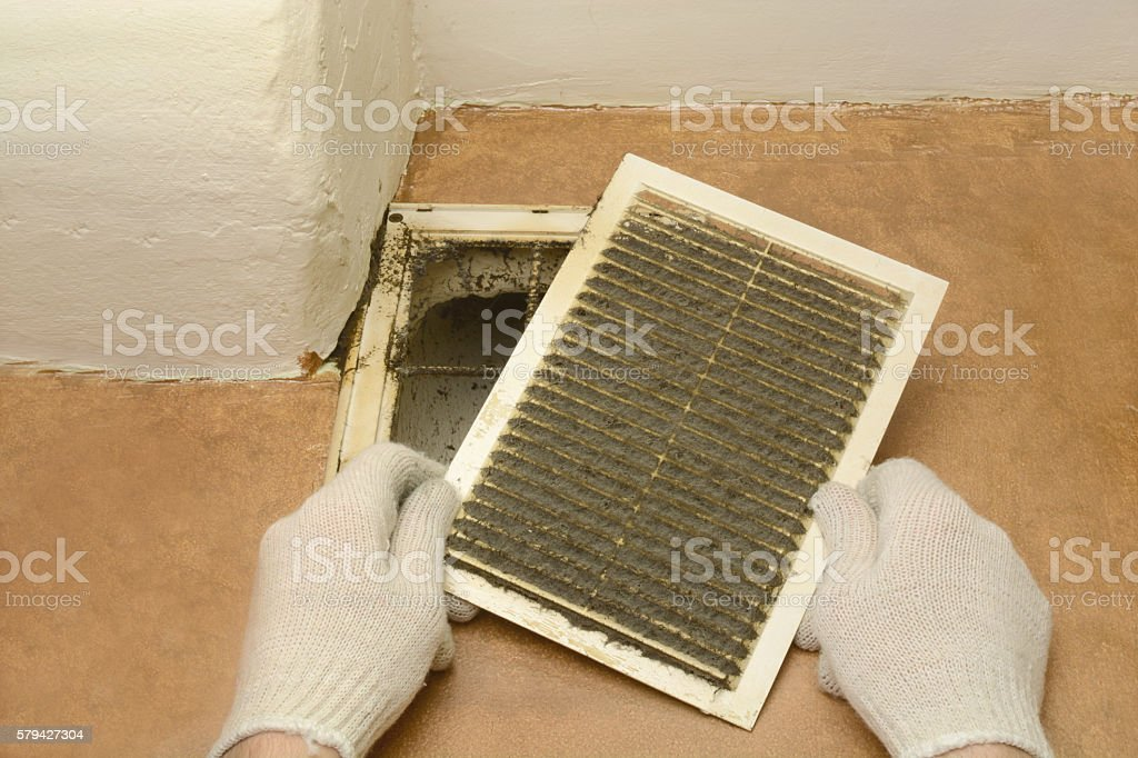 man removes dust ventilation grilles stock photo