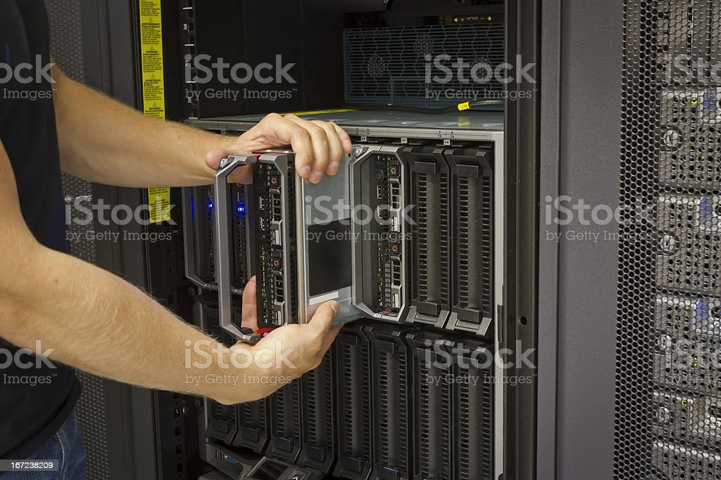 Man removing blade server from control cabinet stock photo