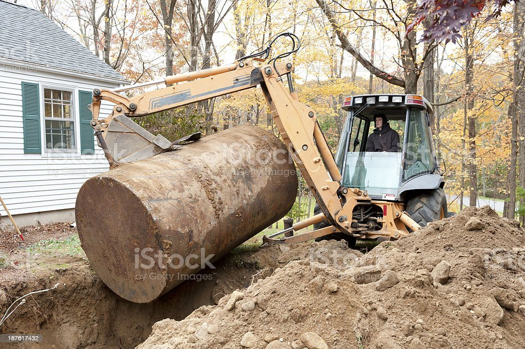 Man removing old oil tank with excavator royalty-free stock photo