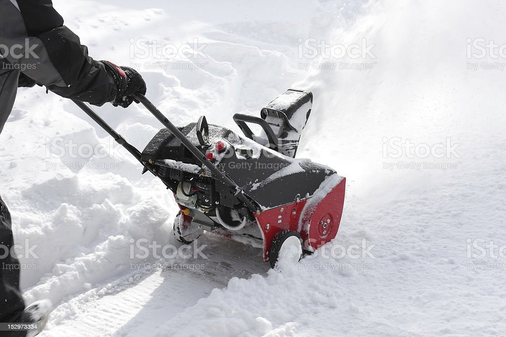 Man removing snow after storm with a snowblower stock photo