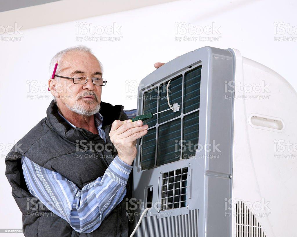 man repairing air conditioning stock photo