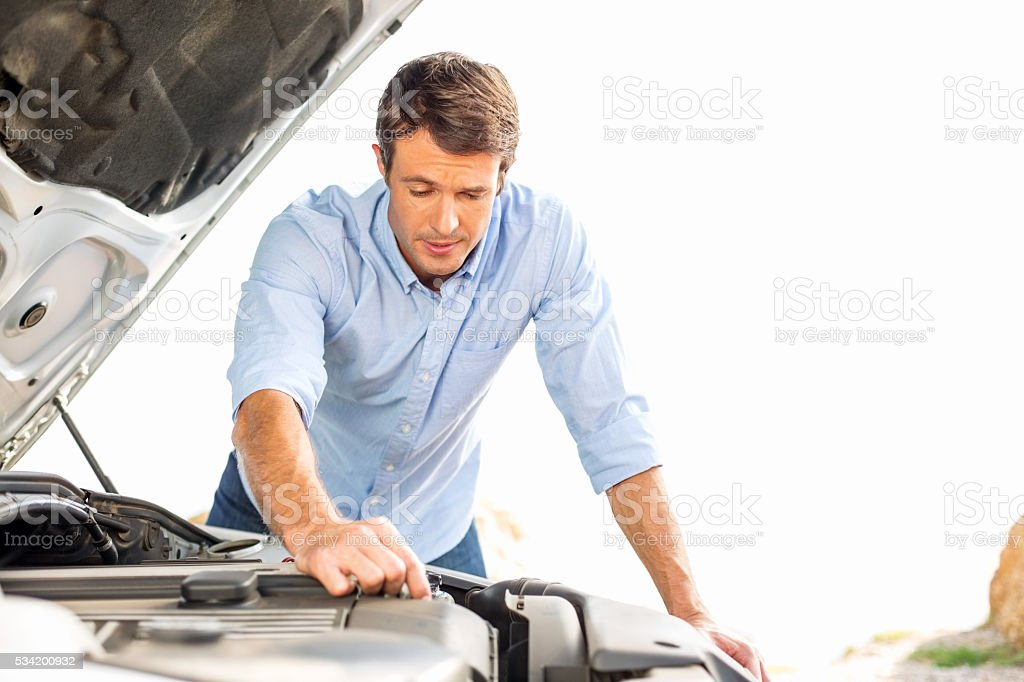 Man Repairing Car Engine Against Clear Sky While On Trip stock photo