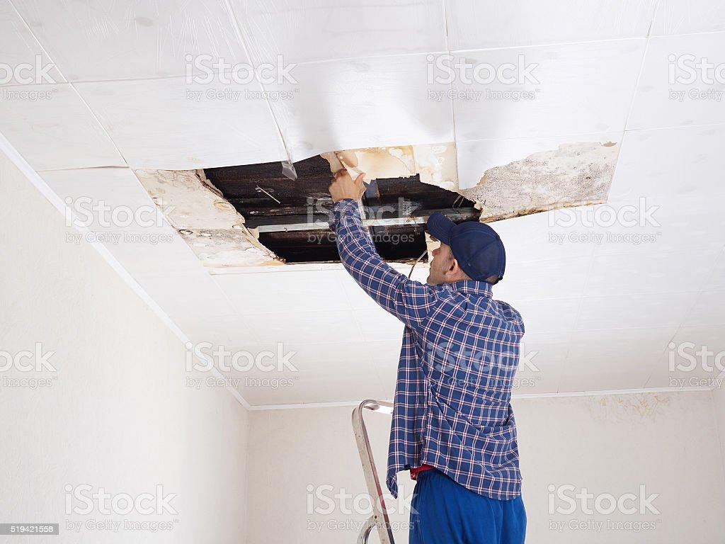 Man repairing collapsed ceiling. stock photo