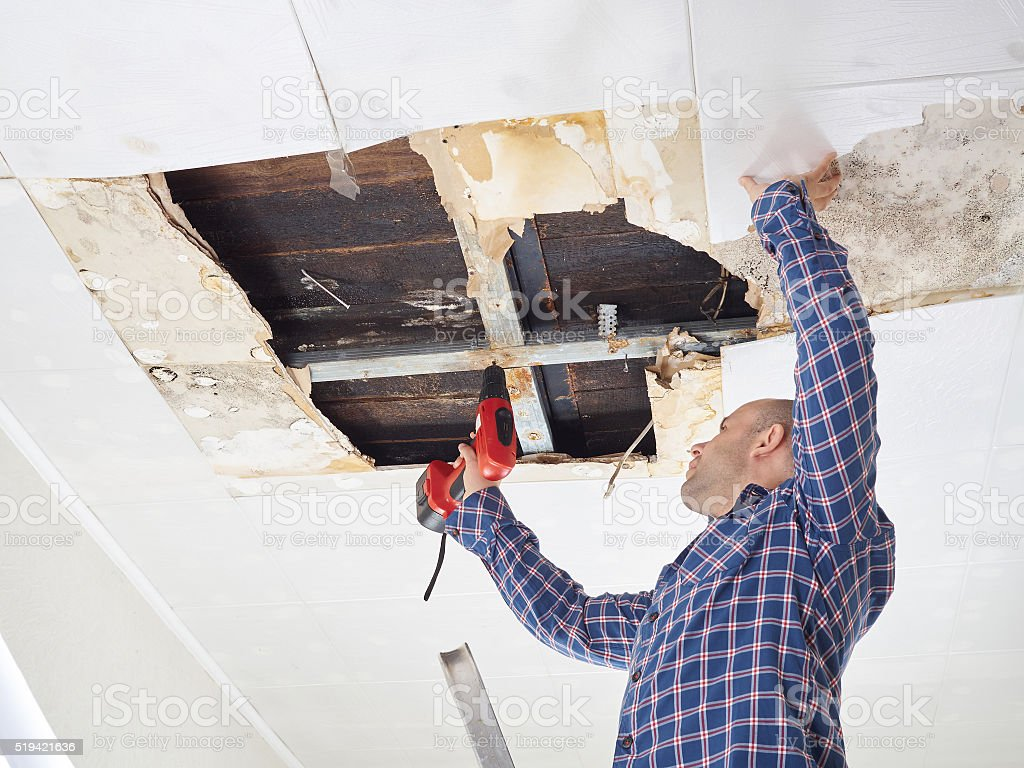 Man repairing collapsed ceiling stock photo