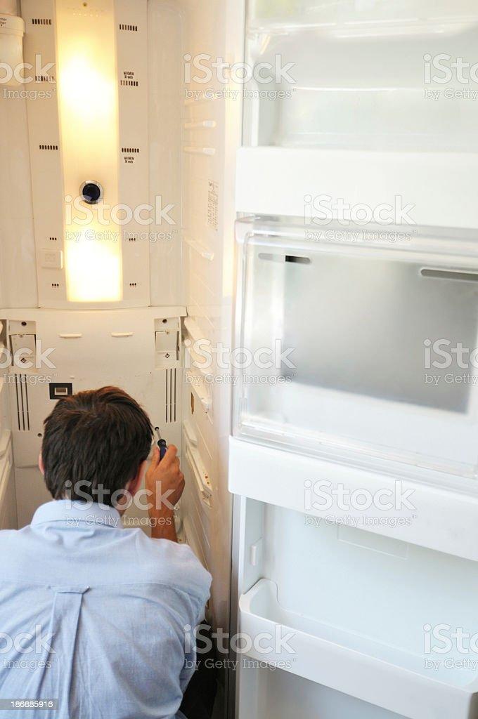 man repairing fridge stock photo
