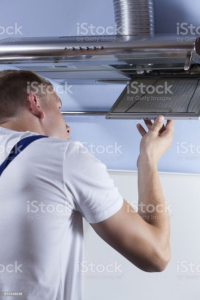 Man repairing kitchen hood stock photo