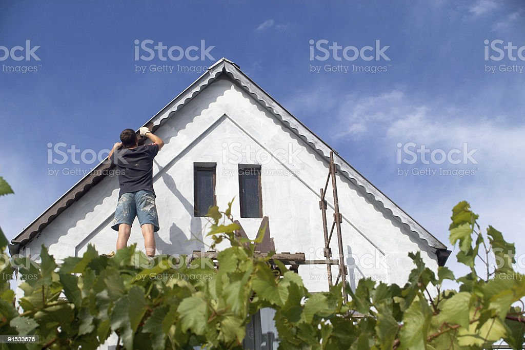 A man repairing the roof of a house royalty-free stock photo