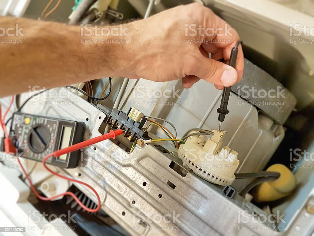 Man repairs washing machine stock photo