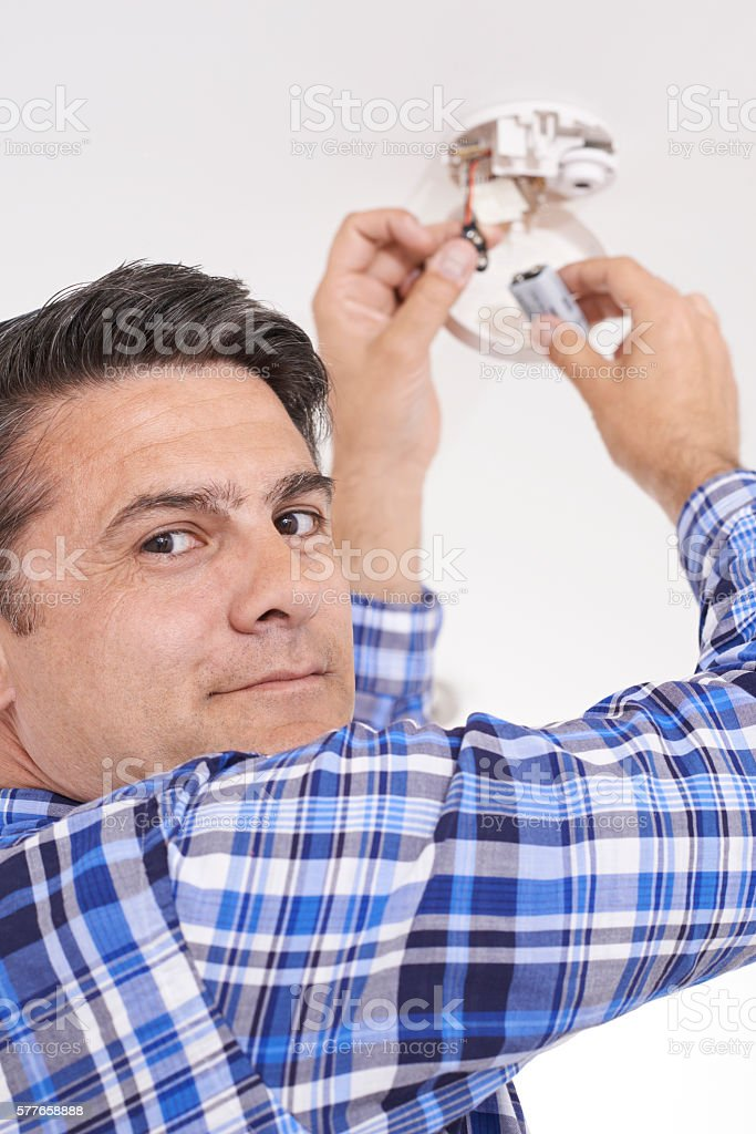 Man Replacing Battery In Home Smoke Alarm stock photo