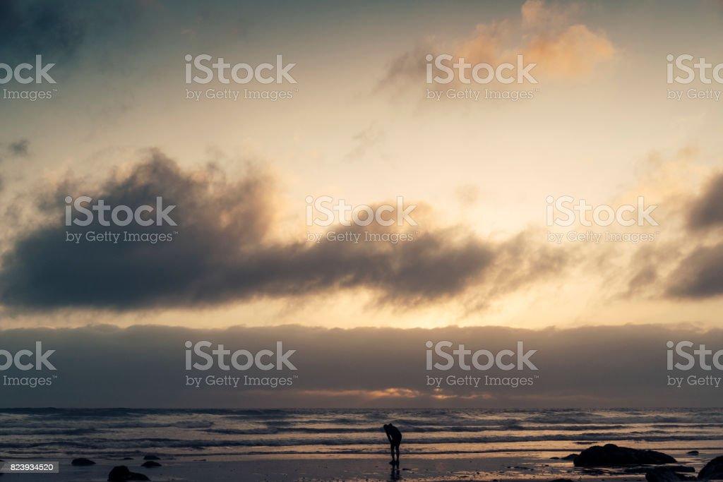 Man resting after a run along the beach. stock photo