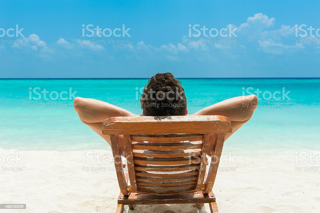 Man resting on beach stock photo