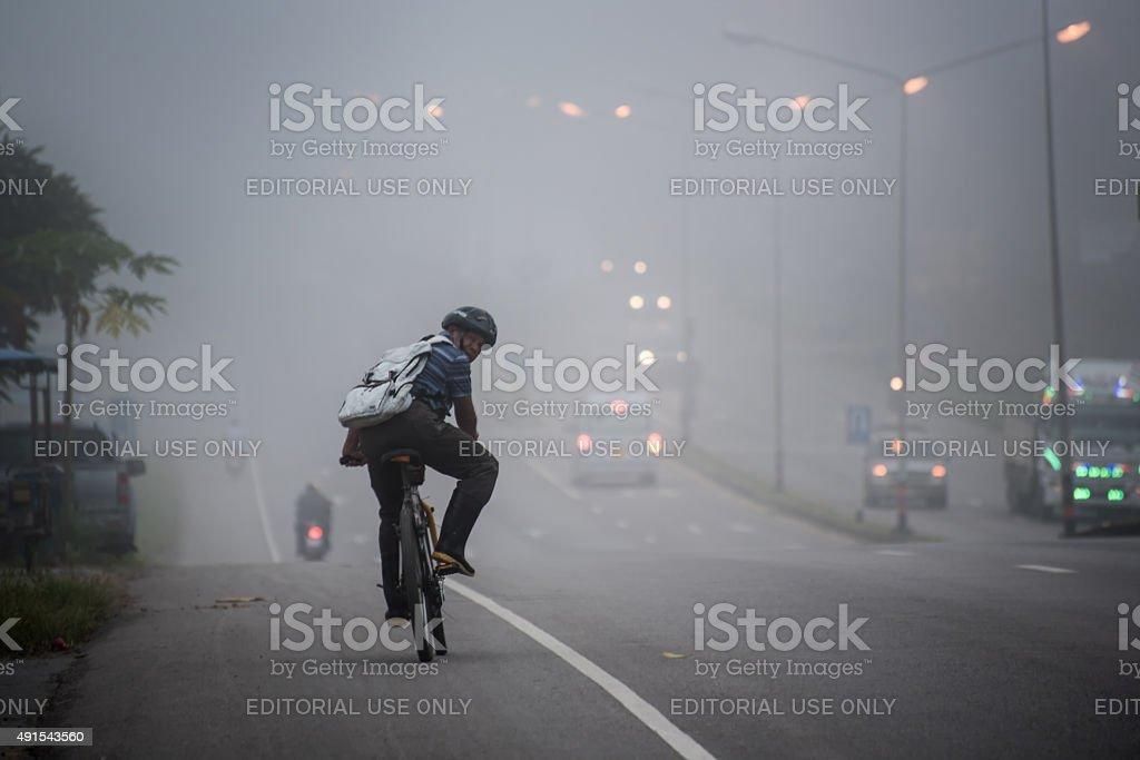 man ride to work in haze stock photo