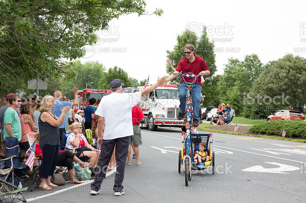 Man rides a unicycle  in July 4th parade in Smithville stock photo