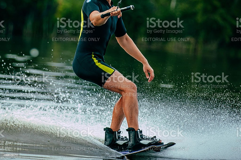 man rides a wakeboard on lake stock photo