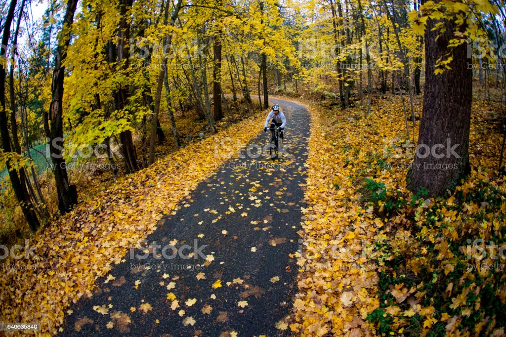 A man rides along a quiet country road in British Columbia, Canada in autumn. stock photo