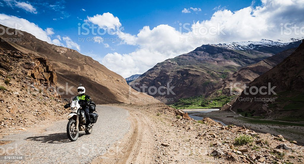 Man rides motorcycle off-road near river stock photo