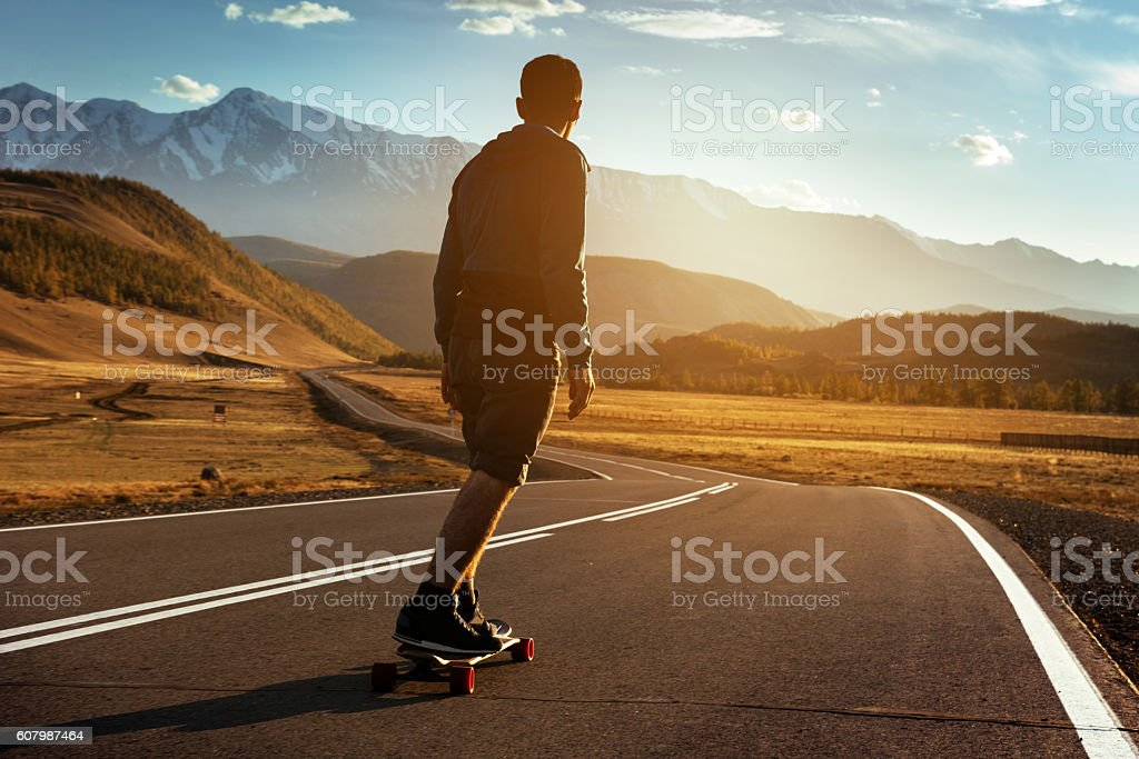 Man rides on longboard at sunset stock photo