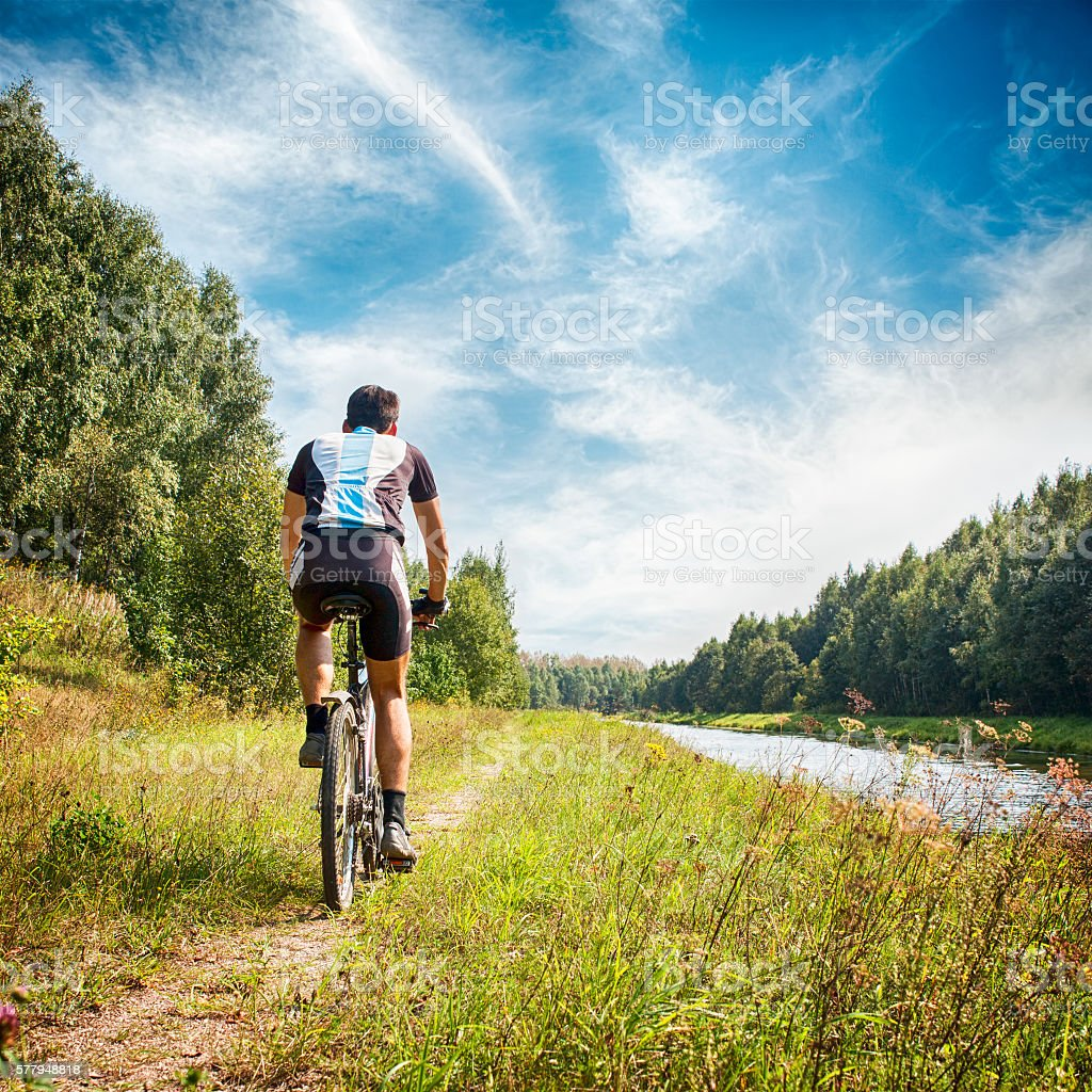 Man Riding a Bicycle on River Bank. Summer Photo. stock photo