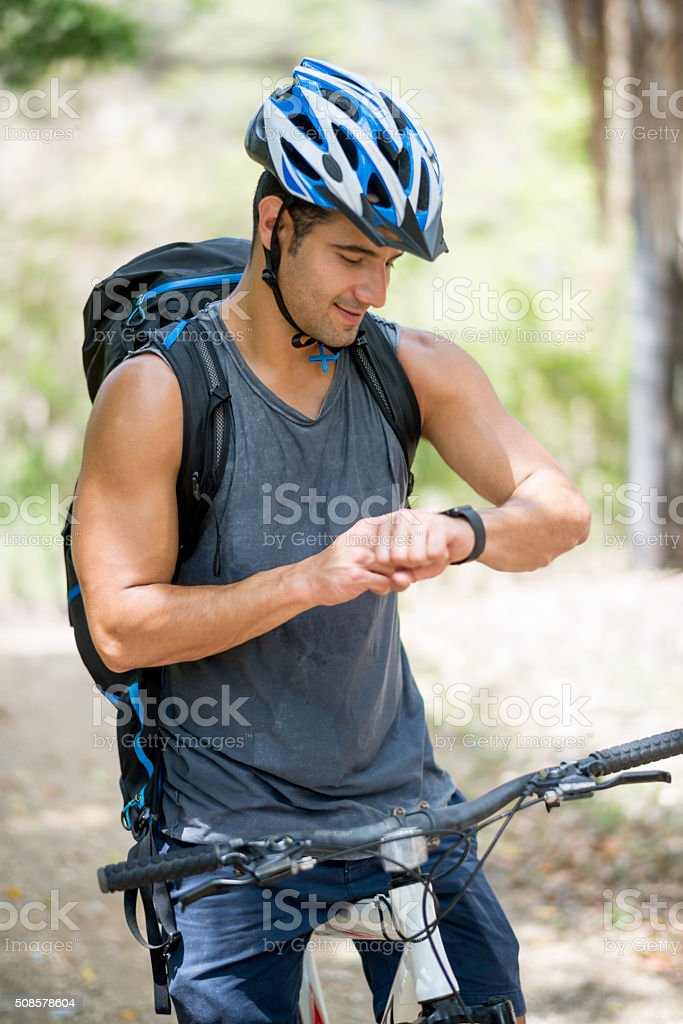 Man riding a bike and using a smart watch stock photo