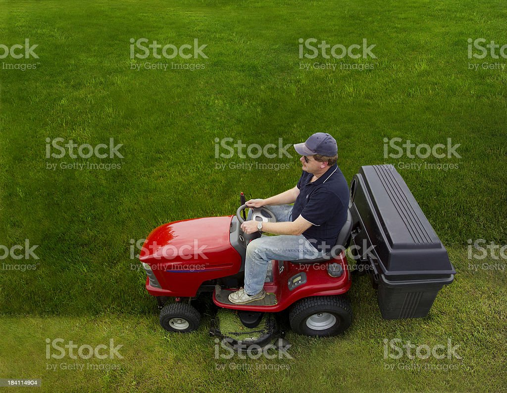 man riding a lawn tractor stock photo