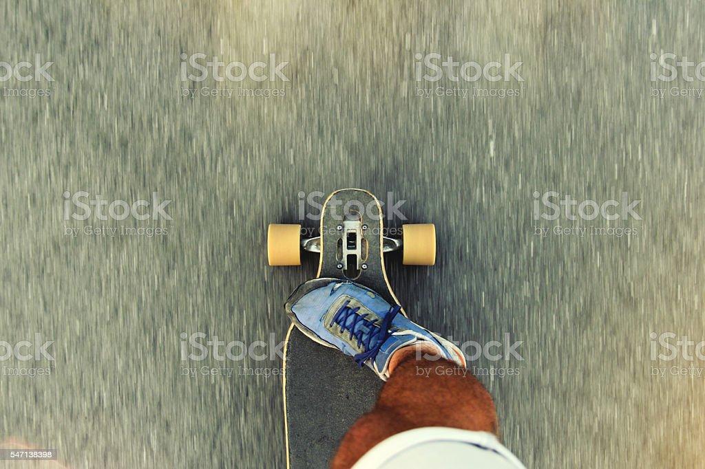 Man riding a longboard stock photo