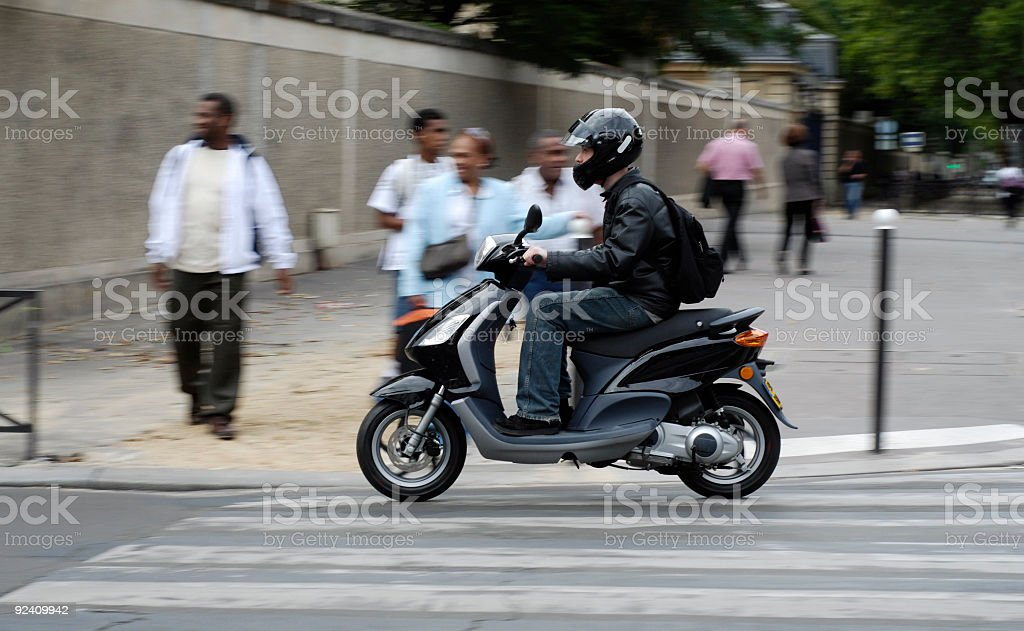 A man riding a motorbike through street royalty-free stock photo